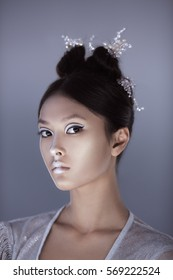 Creative art make-up and hairstyle. Portrait of asian young woman. Beautiful young model Japanese style girl in silver urban clothes with conceptual hairstyle and make-up against gray copy-space