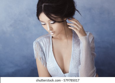 Creative art make-up and hairstyle. Portrait of asian young woman. Beautiful young model Japanese style girl in silver urban clothes with conceptual hairstyle and make-up against blue textured copy