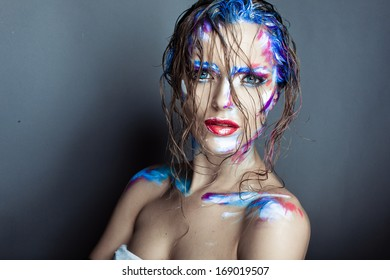 Creative art makeup of a young girl with blue eyes. Strokes of paint on his face and hair. Wet hair on her face