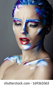 Creative art makeup of a young girl with blue eyes. Strokes of paint on her face and hair