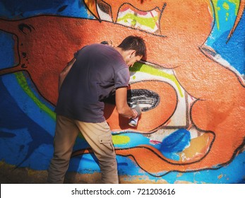 Creative art - teenage boy painting colorful abstract ornament graffiti on street wall with aerosol spray. Back view, overall plan