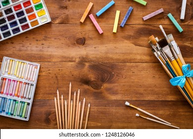 Creative art work accessories tools supplies set on messy desk, paint brushes, paintbox watercolors crayons pencils on brown wooden artistic background, back to school. Top view, flat lay, copy space