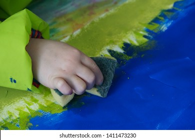 Creative Art Workshop. School kids working with Colors. Hand with Sponge and Paper Sheet on The Colorful Wood Table.