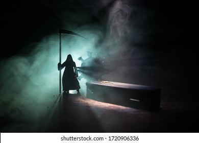 Creative artwork. Miniature wooden coffin and grim reaper on a table with dark background. Victims of coronavirus or loss during coronavirus outbreak concept. Selective focus
