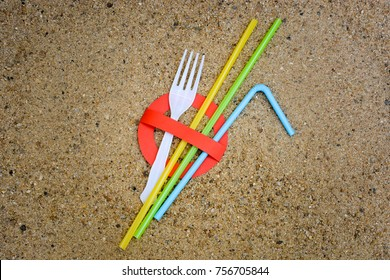 A creative artwork of stop sign over plastic fork and straws on sandy beach background urging people not to use these items to prevent marine pollution. Ban single use plastic.