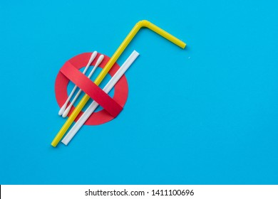 A creative artwork of stop/prohibition sign over plastic cotton bud, straw, stirrer on blue background. Ban single use plastic. Environmental concept.