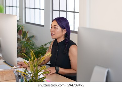 Creative asian woman designer concentrating in trendy office, working at her computer
