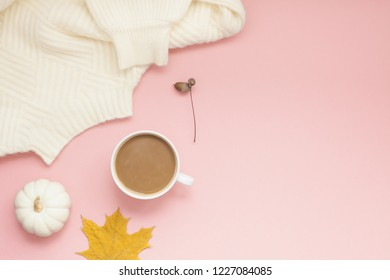Creative autumn flat lay overhead top view coffee milk latte cup on millennial pink background copy space minimal style. Fall season template for feminine blog social media