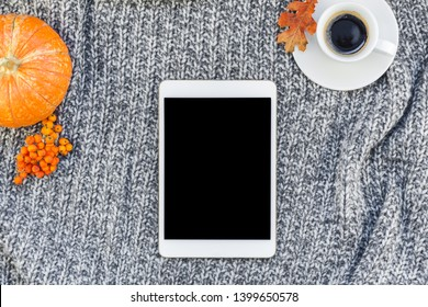 Creative autumn flat lay overhead top view stylish home workspace with tablet notebook coffee cup cozy gray knitted plaid background copy space. Fall season template for feminine blog social media