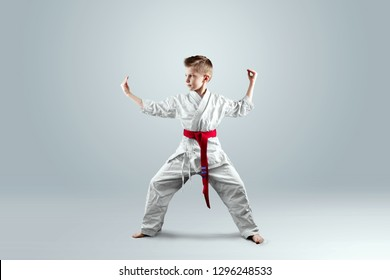 Creative background, a child in a white kimono in a fighting stance, on a light background. The concept of martial arts, karate, sports since childhood, discipline, first place, victory. copy space.