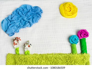 Creative background folded from towels and clothing,  artistic flowers on grass, cloud and sun made from fabric