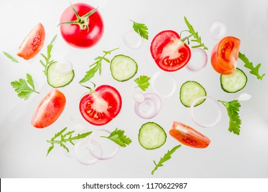 Creative background, layout, concept of fresh healthy diet of salad, fresh raw  vegetables tomatoes parsley onions cucumbers greens, simple pattern on white background