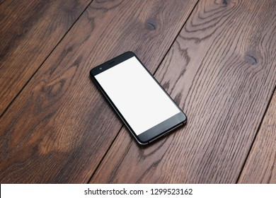 Creative background, smartphone with white screen on the background of wooden table mockup. The concept of preparation for design, mobile applications, mobile games, technology.