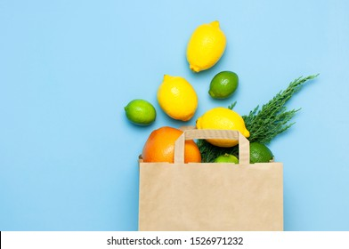 Creative background with tropical fruits. Orange, lemon, lime, grapefruit drop out of paper bag on blue background. Flat lay top view copy space. Food concept, vitamin C, disease prevention, flu