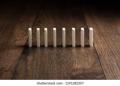 Creative background, white domino, on brown wooden background. Concept of domino effect, chain reaction, risk management, copy space.