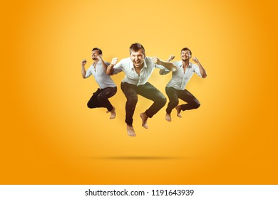 Creative background. Young, handsome man, jumping for joy, very much happy, yellow background. The concept of altero, joy, celebration.