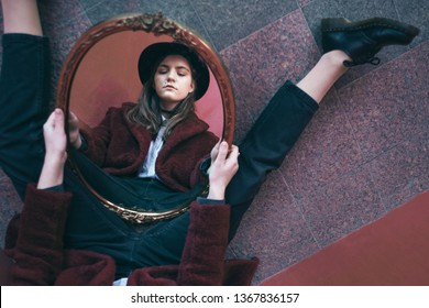 Creative Beautiful teen girl portrait reflection in the mirror. Red colors artistic mood. between dream and reality