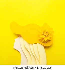 Creative beauty fashion concept photo portrait of woman girl made of paper in hat clothes accessories with natural flower on yellow background.