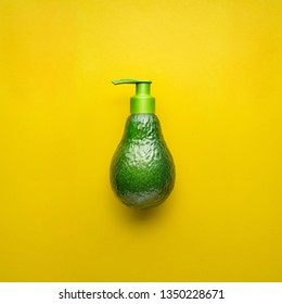 Creative beauty fashion health food concept photo of fresh avocado fruit with cosmetic product cream dispenser on yellow background.