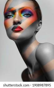 Creative beauty portrait of beautiful woman with rainbow lights on face. Studio portrait