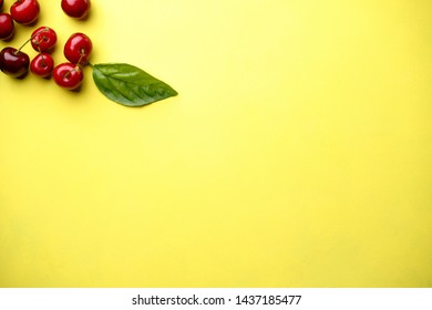 Creative berry layout made of seasonal summer fruits. Healthy food, summertime concept. Cherries on bright yellow background