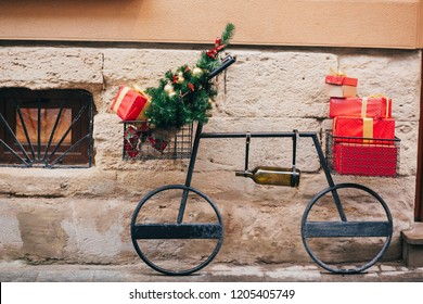 Creative bicycle with christmas tree,red presents, wine bottle in european city street. Stylish christmas street decor, Festive decorations and illumination. Winter holidays. Wine shop