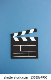 Creative blank clapboard cutout composed on simple blue backdrop