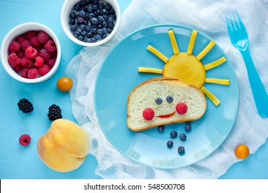 Creative breakfast idea for kids - bread bun with fruit and berry shaped funny cloud with peach sun and blueberry rain , fun with food