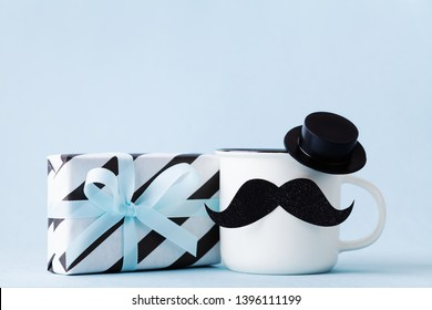 Creative breakfast on Happy Fathers Day with gift or present box and funny face from cup of coffee, hat and moustache.