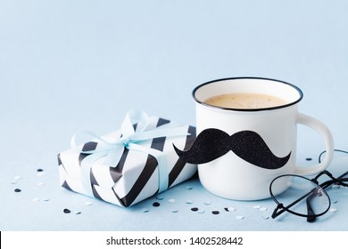 Creative breakfast on Happy Fathers Day with gift box and funny face from cup of coffee and moustache.