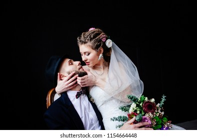 The creative bride with dreadlocks sits on the knees of the groom in a hat in a white vintage chair on a black background, a steep and amusing couple in love