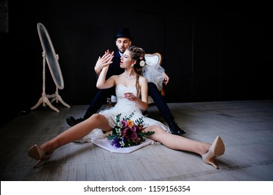 creative bride with dreadlocks sitting on the floor with a bouquet between the legs and a stylish bridegroom in the hat behind, a funny and unusual couple in love