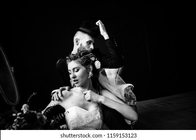 A creative bride with dreadlocks and a stylish bridegroom in a hat hugs her shoulders, a funny and unusual loving couple, a black and white photo