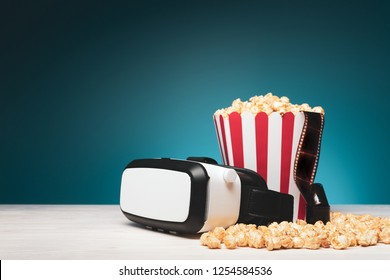 Creative bright arrangement with cinema film in bucket of popcorn and VR headset composed against blue background