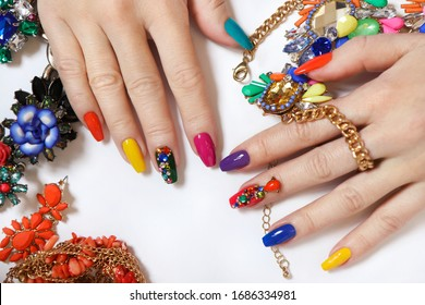 Creative bright saturated manicure on long nails with rhinestones.Nail art on women's hands on a white background with costume jewelry.