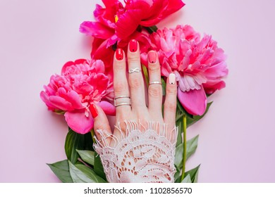 Creative bright trendy summer manicure with nails of different color. Two female hands with art nail design and rings on pink background and fuchsia peony flower bouquet.