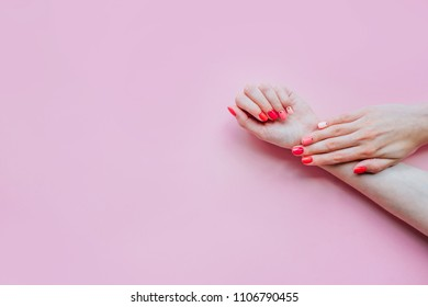 Creative bright trendy summer manicure with nails of different color. Female hands with art nail design on pink background.
