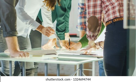 In Creative Bureau. Close-up Shot of a Busy Glass Conference Table and Coworkers Leaning on it in Collective Leap to Find Problem Solutions.