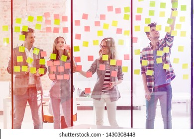 Creative business colleagues using adhesive notes during brainstorming session in office