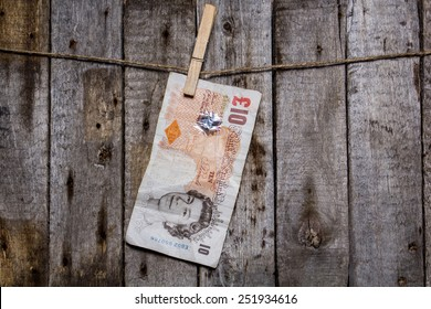 Creative business finance making money concept. Money on a clothespin on a wooden background. Pounds