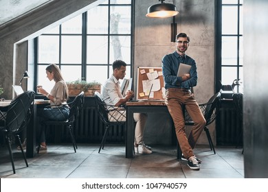 Creative business. Handsome young man in smart casual wear smiling while spending time in the office with his coworkers