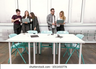 Creative business partners working with laptops behind a white Desk in the office