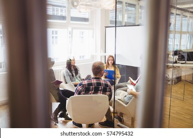 Creative business people discussing in meeting room seen through glass