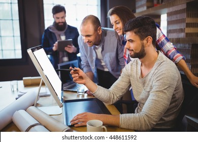 Creative business people discussing over computer at desk in office