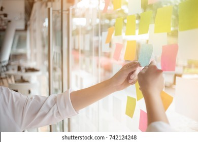 Creative business people reading sticky notes on glass wall with colleague working use post it notes to share idea discussing and teamwork, brainstorming concept.Closeup shot.
