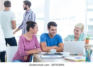 Creative business people using laptop in meeting at office