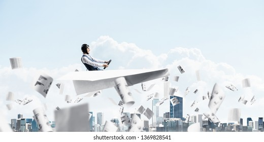 Creative business process concept with funny pilot in leather helmet. Aviator driving big paper plane above falling paper sheets with business infographics. Working with financial documents.