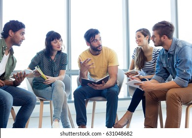 Creative business team discussing with their diaries in office