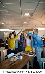 Creative business team giving a high five to each other in office