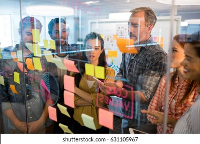 Creative business team looking at sticky notes on glass window in office